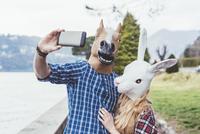 Couple wearing horse and rabbit masks taking smartphone selfie, Lake Como, Italy 11015287417| 写真素材・ストックフォト・画像・イラスト素材|アマナイメージズ