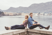 Portrait of young couple sitting back to back on harbour wall, Lake Como, Italy 11015287422| 写真素材・ストックフォト・画像・イラスト素材|アマナイメージズ