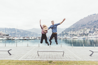 Young couple on waterfront jumping mid air,  Lake Como, Italy