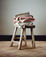 Folded blankets on small wooden stool