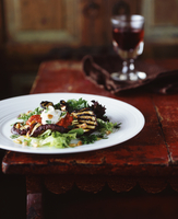 Grilled aubergine and pine nut salad with glass of red wine