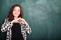 Girl gesturing heart shaped hands beside 'Love' word on blackboard