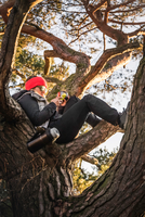 Woman relaxing and using mobile phone on treetop, Augsburg, Bavaria, Germany 11015287761| 写真素材・ストックフォト・画像・イラスト素材|アマナイメージズ