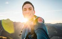 Hiker taking selfie in mountains on sunny day, Kleinwalsertal, Austria