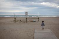Girl on beach looking away at ocean 11015287983| 写真素材・ストックフォト・画像・イラスト素材|アマナイメージズ