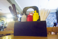 Condiments in trug on cafe table