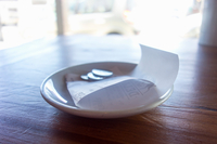 Saucer on table with receipt and coins