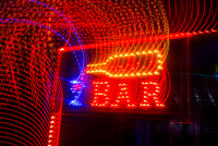 Long exposure image of light trails on neon bar sign