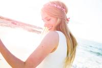 Young woman on beach, dancing, smiling 11015288235| 写真素材・ストックフォト・画像・イラスト素材|アマナイメージズ