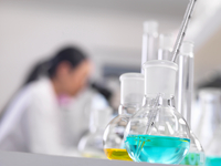 A scientist looking down a microscope with a chemical formula in the foreground