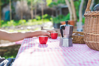 Man's hand with espresso cup at table in garden