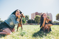 Two young women playing with pit bull terriers in urban park