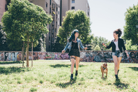 Two young women walking with pit bull terrier in urban park