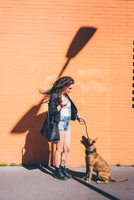 Young woman with dreadlocks looking at pit bull terrier in front of orange wall