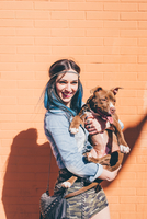 Young woman with dip dyed blue hair holding pit bull in front of orange wall