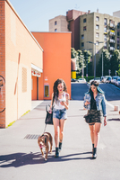 Two young women walking pit bull in urban housing estate