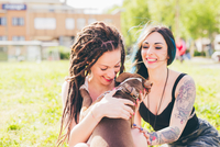 Tattooed young women playing with pit bull terrier in urban park