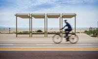 Blurred motion of cyclist cycling along coastal road, Cagliari, Italy