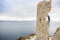 Male rock climber climbing ruined tower on coast, Cagliari, Italy