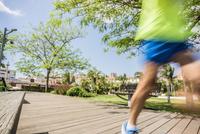 Blurred motion of runner running on park boardwalk
