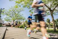 Blurred motion of runners running on park boardwalk