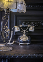 Art deco lamp and vintage telephone on antique sideboard
