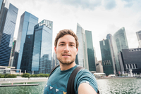 Tourist posing in front of Singapore skyline, Marina Bay