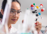 Scientist using molecular model to understand chemical formula