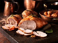 Boned roasted turkey breasts and thighs, roasted apples and vegetables, vintage wooden chopping board, metal bowls, pots and pan
