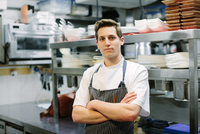 Portrait of young male chef with arms folded in kitchen