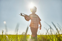 Boy in sunlit field playing with toy airplane