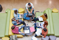Overhead view of seven male and female students brainstorming in higher education college study space