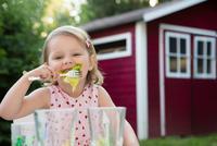 Portrait of female toddler eating salad in garden, Bavaria, Germany