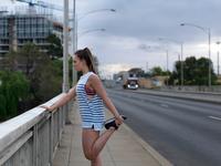 Young female runner stretching legs on highway bridge at dawn 11015289376| 写真素材・ストックフォト・画像・イラスト素材|アマナイメージズ