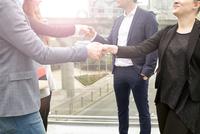 Neck down view businesswomen and men shaking hands on city footbridge, London, UK