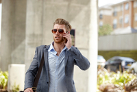 Young businessman wearing sunglasses talking on smartphone outside office, London, UK