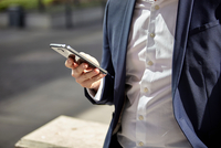 Mid section of businessman texting on smartphone in city