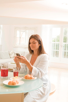 Mature woman at breakfast table reading mobile phone texts 11015290122| 写真素材・ストックフォト・画像・イラスト素材|アマナイメージズ