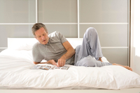 Senior man reclining on bed reading magazine and listening to earphones