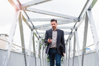 Mature businessman walking on footbridge texting on smartphone 11015290210| 写真素材・ストックフォト・画像・イラスト素材|アマナイメージズ
