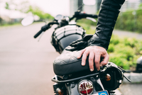 Hand of male motorcyclist leaning on motorcycle