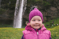 Portrait of young girl in field, waterfall in background, Seljalandsfoss, Iceland