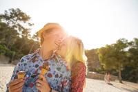 Couple holding ice cream cones hugging, Majorca, Spain