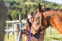 Woman tethering horse to fence post