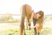 Woman checking horse's hoof 11015290855| 写真素材・ストックフォト・画像・イラスト素材|アマナイメージズ