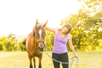 Woman in field stroking horse on tether