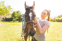 Woman in field holding tethered horse smiling