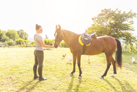 Woman in field stroking horse