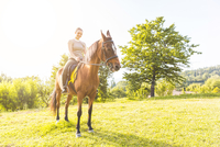 Woman riding horse looking at camera smiling 11015290878| 写真素材・ストックフォト・画像・イラスト素材|アマナイメージズ