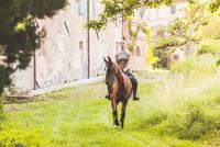 Woman riding horse looking at camera smiling 11015290880| 写真素材・ストックフォト・画像・イラスト素材|アマナイメージズ